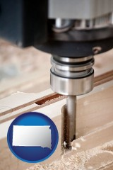 south-dakota map icon and a CNC milling machine cutting wood