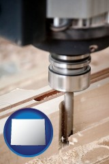 wyoming map icon and a CNC milling machine cutting wood