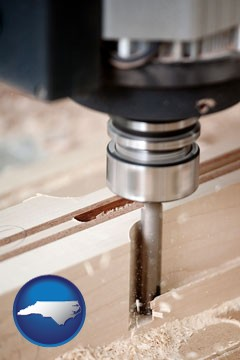 a CNC milling machine cutting wood - with North Carolina icon